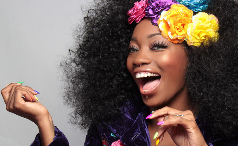 woman with colorful flowers in her hair and a big smile with white teeth